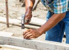 Travailleur martelant le clou dans le bois Photo stock