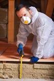 Travailleur mesurant l'épaisseur de l'isolation thermique photo libre de droits