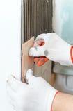 Travailleur mettant des tuiles sur le mur dans la cuisine Photos stock