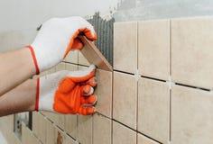 Travailleur mettant des tuiles sur le mur dans la cuisine Photos libres de droits