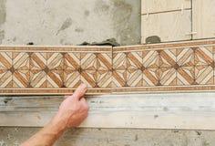 Travailleur mettant des tuiles sur le plancher image stock