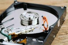 Travailleur miniature ou personnel professionnel creusant sur HDD, unité de disque dur employant comme exploitation de données, r image libre de droits