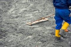 Travailleur nivelant avec la truelle en bois le béton ou le ciment versé frais photos stock