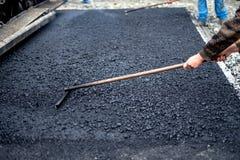 Travailleur nivelant l'asphalte frais sur un site de construction de routes, bâtiment industriel images stock