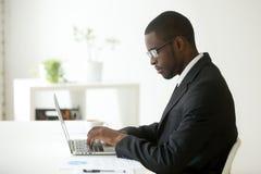 Travailleur noir focalisé travaillant à l'ordinateur portable sur le lieu de travail de société photos libres de droits