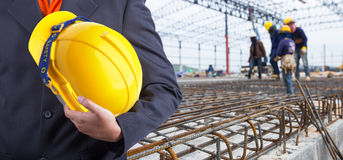 Travailleur ou ingénieur se tenant dans le casque jaune de mains Images stock