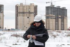 Travailleur ou ingénieur tenant le dessin dans les mains et la lecture il sur le fond de nouveaux immeubles et construction Image libre de droits