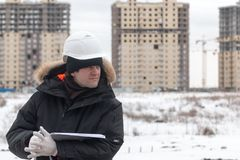 Travailleur ou ingénieur tenant le dessin dans les mains et la lecture il sur le fond de nouveaux immeubles et construction Photo stock