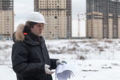 Travailleur ou ingénieur tenant le dessin dans les mains et la lecture il sur le fond de nouveaux immeubles et construction Image stock