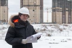 Travailleur ou ingénieur tenant le dessin dans les mains et la lecture il sur le fond de nouveaux immeubles et construction Photos libres de droits