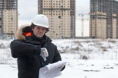 Travailleur ou ingénieur tenant le dessin dans les mains et la lecture il sur le fond de nouveaux immeubles et construction Photographie stock
