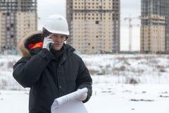 Travailleur ou ingénieur tenant le dessin dans les mains et le téléphone portable d'utilisations sur le fond de nouveaux immeuble Photo stock