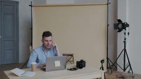 Travailleur ou photographe créatif élégant attirant parlant sur le smartphone et s'asseyant dans le lieu de travail moderne de lu clips vidéos