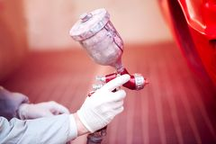 Travailleur peignant une voiture rouge dans la cabine de peinture utilisant le pistolet de pulvérisation Photo libre de droits
