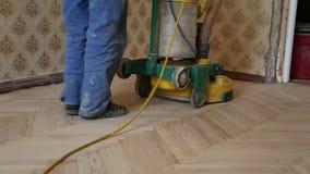 Travailleur polissant le vieux plancher de parquet en bois banque de vidéos