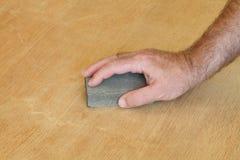Travailleur ponçant la planche en bois Images stock