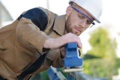 Travailleur ponçant la vieille peinture de la barrière en bois Photo libre de droits