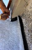 Travailleur posant avec le liquide bitumeux de gaine de brosse photos libres de droits