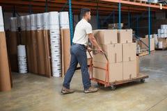 Travailleur poussant le chariot avec des boîtes Image stock