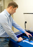 Travailleur près de machine de gravure de laser image libre de droits