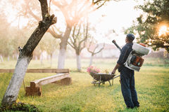 travailleur pulvérisant les pesticides organiques pour le traitement de jardin Images libres de droits