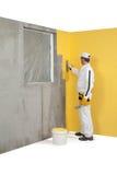 Travailleur répandant un plâtre sur un coin-mur Image stock