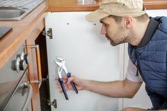 Travailleur réparant l'évier dans la cuisine photos libres de droits