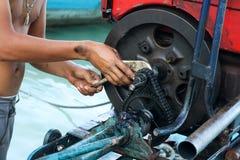 Travailleur réparant la vitesse à chaînes du moteur diesel de bateau de Long-queue Photos stock