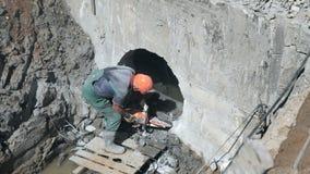 Travailleur réparant le collecteur de construction banque de vidéos