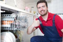 Travailleur réparant le lave-vaisselle dans la cuisine photo stock