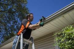 Travailleur réparant une gouttière sur clients à la maison Photo stock