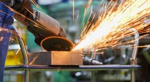 Travailleur rectifiant en acier par la machine de meulage électrique images stock