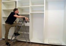 Travailleur regardant la garde-robe Concept d'ensemble de Cabinet Images stock