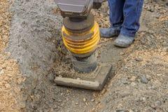 Travailleur rendant la literie de sable avec la dame mécanique compacte Images stock