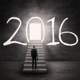 Travailleur se tenant sur les escaliers avec les numéros 2016 Photo libre de droits