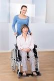 Travailleur social avec la femme supérieure handicapée dans le fauteuil roulant Image stock