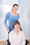 Travailleur social avec la femme supérieure handicapée dans le fauteuil roulant Photographie stock libre de droits