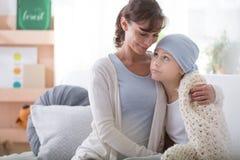 Travailleur social de sourire soutenant l'enfant malade avec le cancer portant le foulard bleu images libres de droits