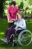 Travailleur social donnant la poire à la femme supérieure handicapée Images libres de droits