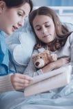 Travailleur social lisant un livre à une fille malade avec le jouet de peluche dans le Cl Photo libre de droits