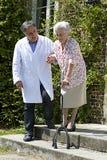Travailleur social masculin aidant le patient supérieur avec un bâton de marche Photographie stock libre de droits