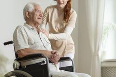 Travailleur social soutenant l'homme plus âgé malade dans le fauteuil roulant pendant le s Photo stock