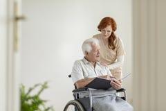 Travailleur social soutenant l'homme plus âgé paralysé dans un fauteuil roulant avec photos libres de droits