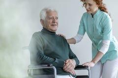 Travailleur social soutenant l'homme supérieur handicapé heureux dans un fauteuil roulant i photos stock