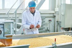 Travailleur supérieur surveillant la production de la nourriture photographie stock