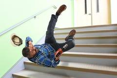 Travailleur supérieur tombant sur des escaliers Photo libre de droits