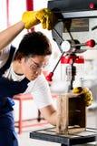 Travailleur sur la foreuse dans l'atelier Photo stock