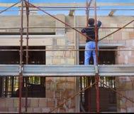 Travailleur sur la maçonnerie de bâtiment d'échafaudage Photos libres de droits