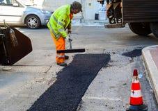 Travailleur sur la machine de asphaltage de machine à paver Photos stock