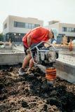 Travailleur sur le chantier de construction avec le compacteur vibrant pour le compactage de sol ou la dame de terre images stock
